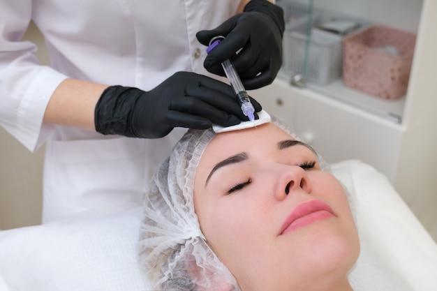 Injections cosmétiques pour le rajeunissement de la peau. le cosmétologue injecte une seringue dans la peau d'une jeune femme.