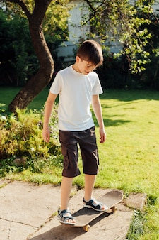 Innocent garçon jouant à la planche à roulettes dans le parc