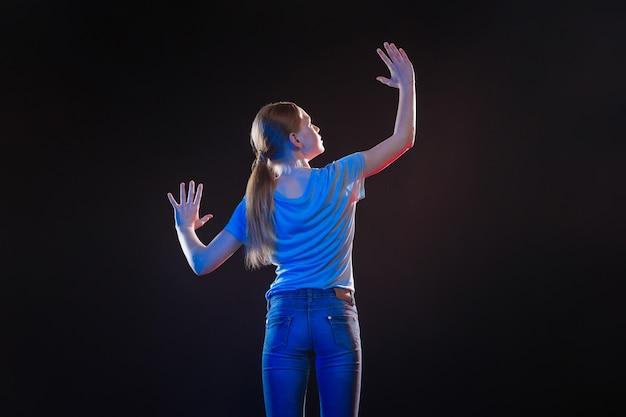 Innovations modernes. agréable femme ravie en regardant ses mains tout en touchant l'écran virtuel