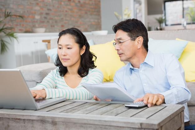 Inquiet couple vérifiant les factures dans le salon