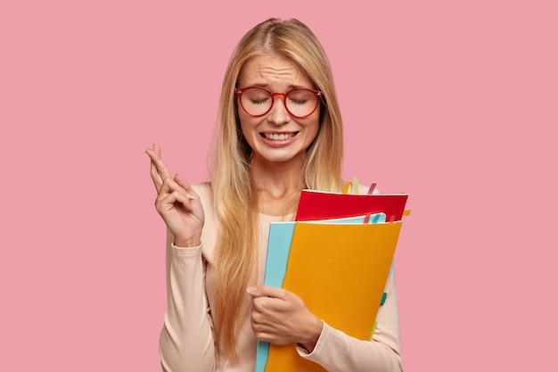 Inquiet étudiant blond stressant posant contre le mur rose