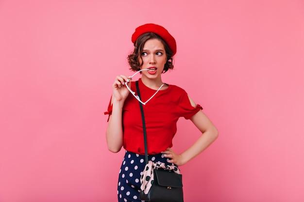Inquiet femme française posant. fille bouclée caucasienne porte un béret rouge.
