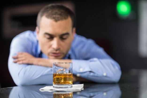 Inquiet homme d'affaires buvant une bière