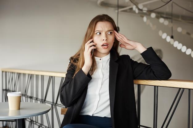Inquiet jeune femme d'affaires au café parler par téléphone