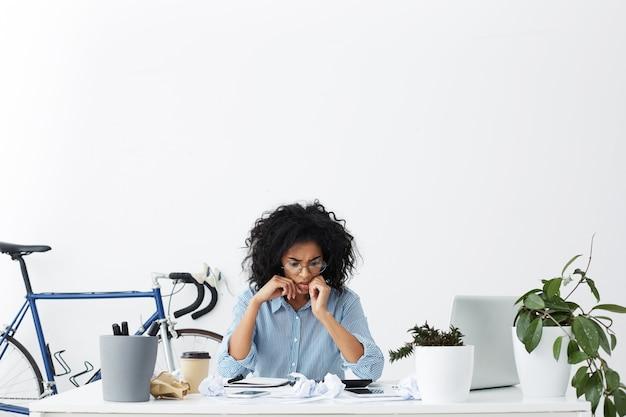Inquiet de jeune femme employée de bureau aux cheveux bouclés ayant un regard désespéré anxieux