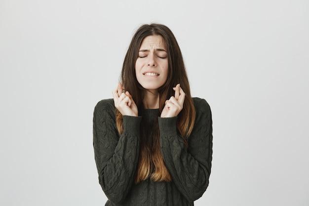 Inquiet jeune femme mignonne faisant voeu avec les yeux fermés et les doigts croisés