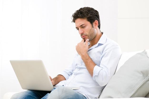 Inquiet jeune homme en regardant son ordinateur portable avec une expression pensive