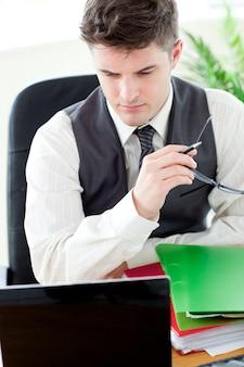 Inquiet médecin de sexe masculin en regardant son ordinateur portable