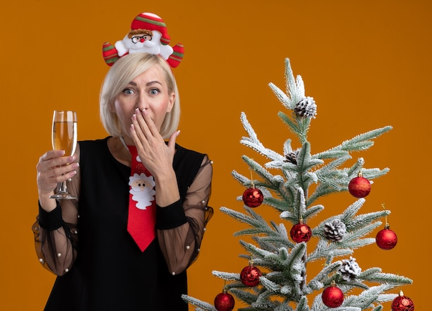 Inquiète femme blonde d'âge moyen portant un serre-tête et une cravate du père noël debout près d'un arbre de noël décoré tenant un verre de champagne regardant en gardant la main sur la bouche isolée sur un mur orange
