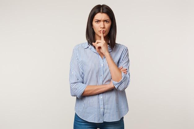 Inquiète inquiète belle fille aux cheveux noirs avec un teint basané faisant un geste de silence mettant le doigt sur les lèvres, demande à rester calme, garder le secret, isolé