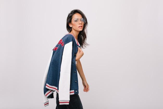 Inquiète jeune femme brune à grosses lunettes portant une veste de sport colorée sur l'épaule. malheureuse fille européenne aux cheveux brillants posant avec une expression de visage fatigué.