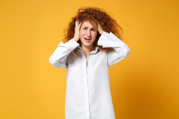 Insatisfait bouleversé jeune femme rousse fille en chemise blanche posant isolé sur mur orange jaune