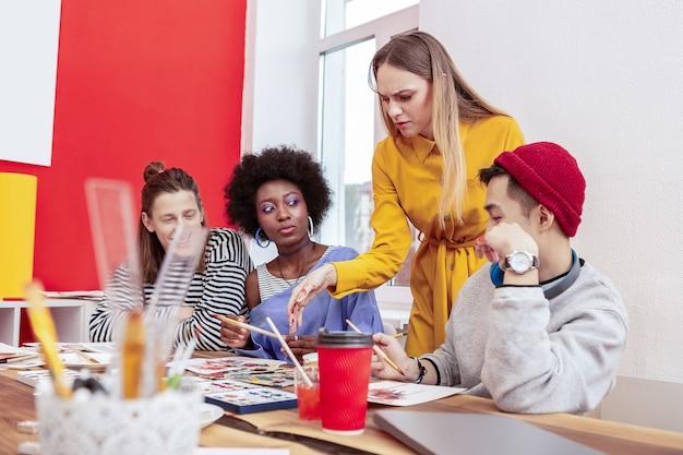 Insatisfait du comportement. jeune enseignant aux cheveux blonds se sentant insatisfait du comportement des élèves