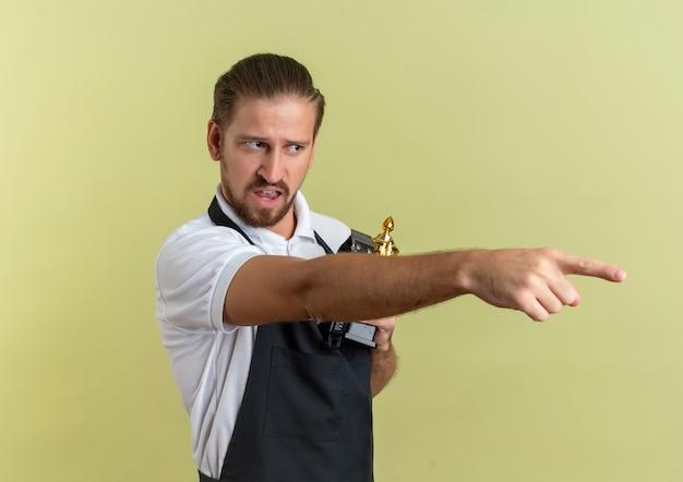 Insatisfait jeune beau coiffeur tenant des tondeuses à cheveux et coupe du gagnant à la recherche et pointant sur le côté isolé sur fond vert olive avec espace copie