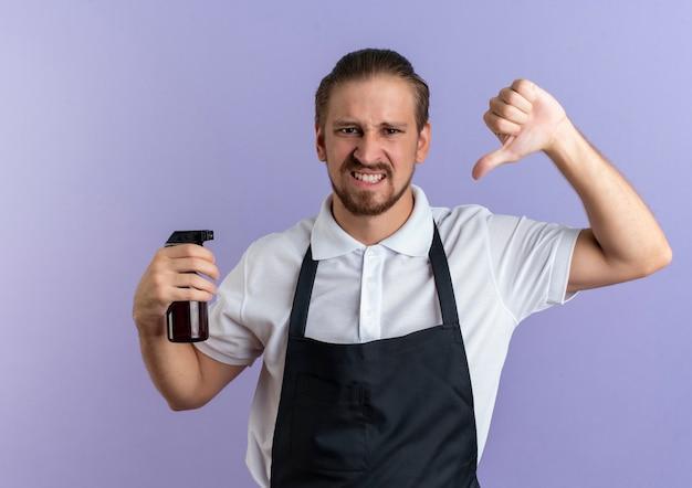 Insatisfait jeune beau coiffeur en uniforme tenant un flacon pulvérisateur et montrant le pouce vers le bas isolé sur fond violet