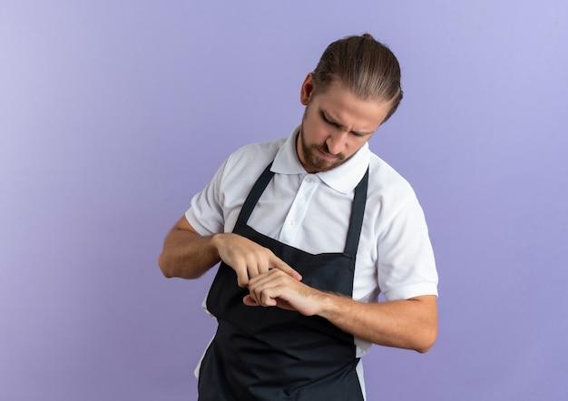 Insatisfait jeune beau coiffeur en uniforme touchant sa main avec le doigt faire semblant de regarder swatch isolé sur fond violet avec copie espace