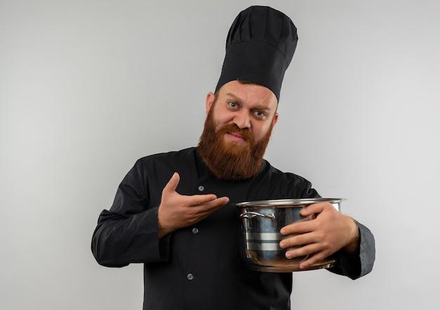 Insatisfait jeune beau cuisinier en uniforme de chef tenant et pointant avec la main au pot isolé sur espace blanc