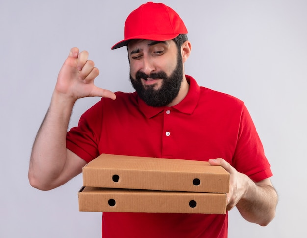 Insatisfait jeune beau livreur caucasien vêtu d'un uniforme rouge et cap tenant et regardant des boîtes de pizza et montrant le pouce vers le bas isolé sur fond blanc