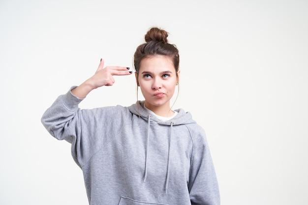 Insatisfait jeune femme aux cheveux assez longs portant ses cheveux bruns en noeud tout en posant sur fond blanc, faisant la moue tout en levant la main avec le geste du pistolet