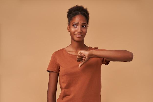 Insatisfait jeune femme bouclée à la peau sombre vêtue d'un t-shirt en bronze levant la main avec un geste de dégoût et grimaçant avec mécontentement face en se tenant debout sur beige