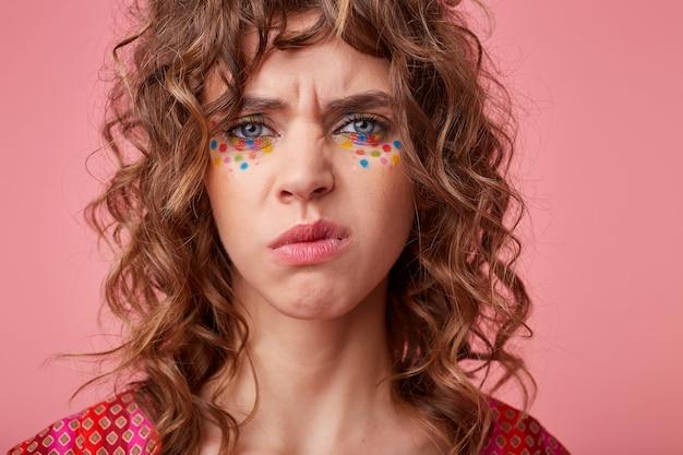 Insatisfait jeune femme brune aux yeux bleus avec des points multicolores sur son visage fronçant les sourcils et à la moue, isolé