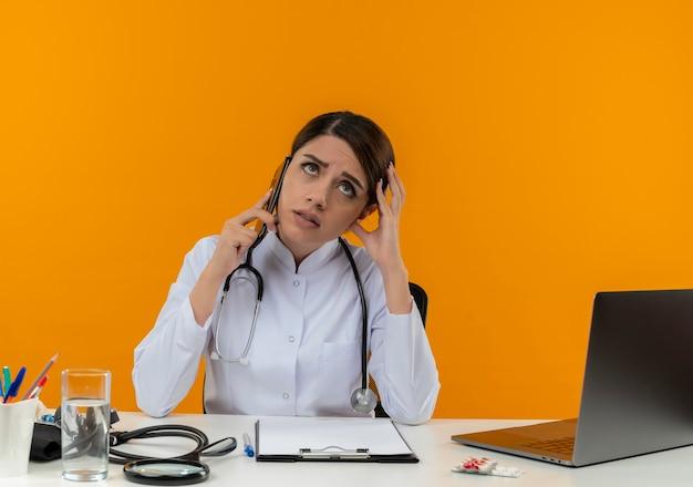 Insatisfait jeune femme médecin portant une robe médicale et un stéthoscope assis au bureau avec des outils médicaux et un ordinateur portable parlant au téléphone touchant la tête en levant isolé