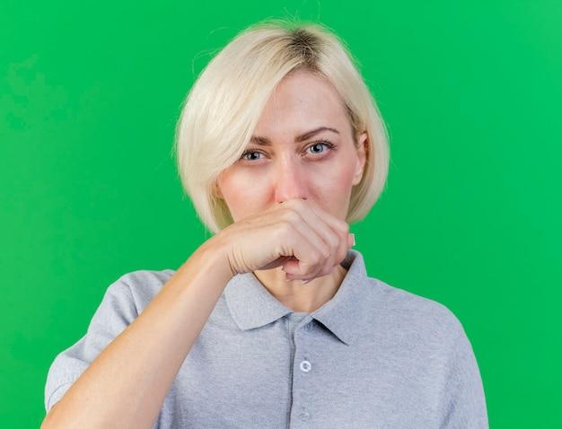 Insatisfait jeune femme slave malade blonde essuie le nez avec la main isolé sur un mur vert avec espace de copie