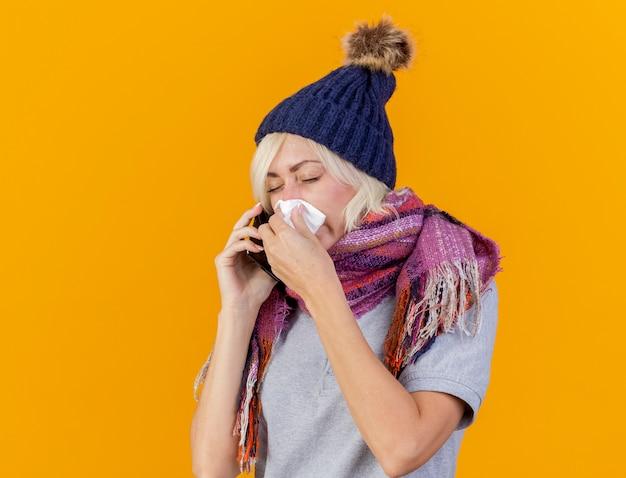 Insatisfait jeune femme slave malade blonde portant chapeau d'hiver et écharpe essuie le nez avec du tissu et parle au téléphone isolé sur un mur orange avec espace de copie