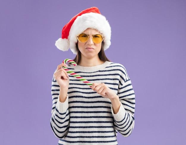 Insatisfait jeune fille caucasienne à lunettes de soleil avec bonnet de noel tenant la canne en bonbon