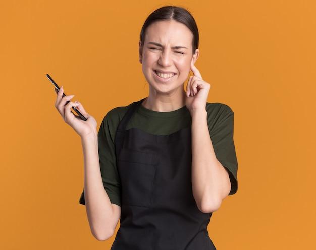 Insatisfait jeune fille de coiffeur brune en uniforme ferme l'oreille avec le doigt et tient le téléphone sur orange