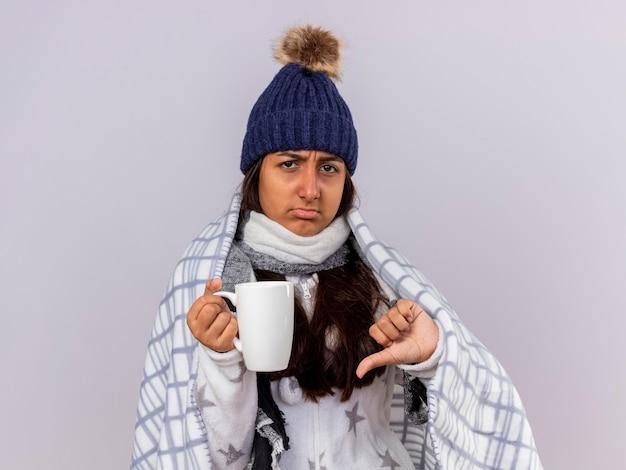 Insatisfait jeune fille malade portant chapeau d'hiver avec écharpe enveloppée dans un plaid tenant une tasse de thé montrant le pouce vers le bas