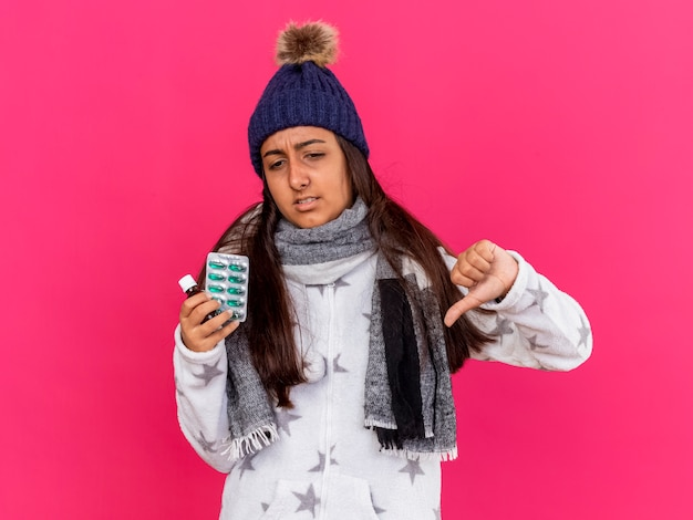 Insatisfait jeune fille malade portant chapeau d'hiver avec écharpe tenant des médicaments dans une bouteille en verre montrant le pouce vers le bas isolé sur fond rose