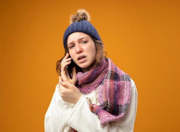 Insatisfait jeune fille malade portant une robe blanche et un chapeau d'hiver avec écharpe parle au téléphone isolé sur mur orange