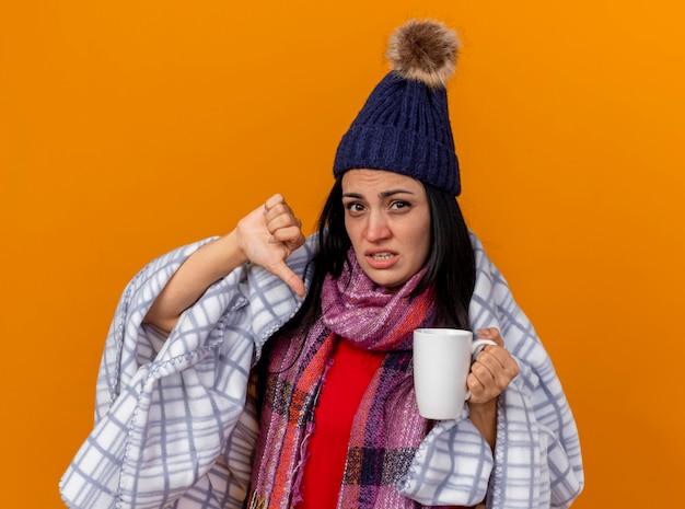 Insatisfait jeune fille malade de race blanche portant chapeau d'hiver et écharpe enveloppée dans un plaid tenant une tasse de thé montrant le pouce vers le bas isolé sur un mur orange