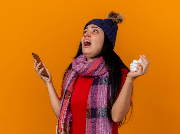 Insatisfait Jeune Fille Malade De Race Blanche Portant Un Chapeau D'hiver Et Une écharpe Tenant Un Téléphone Mobile Et Une Serviette En Levant Isolé Sur Un Mur Orange Photo gratuit