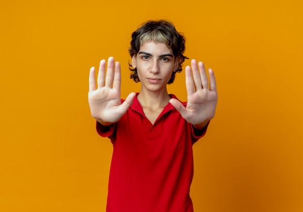 Insatisfait jeune fille de race blanche avec coupe de cheveux de lutin étendant les mains gesticulant arrêter isolé sur fond orange avec copie espace