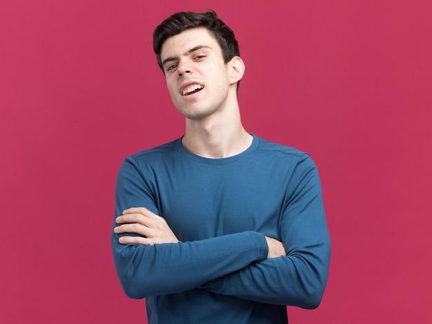 Insatisfait jeune garçon caucasien brune debout avec les bras croisés regardant la caméra sur rose