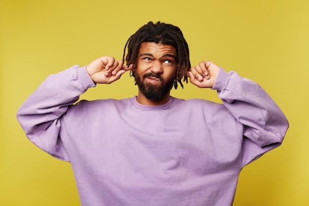 Insatisfait jeune homme barbu aux cheveux bruns avec la peau foncée couvrant ses oreilles et le visage grimaçant tout en essayant d'éviter les sons ennuyeux, isolés sur fond jaune