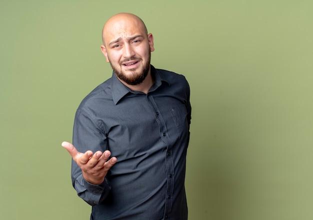 Insatisfait jeune homme de centre d'appels chauve montrant la main vide isolé sur fond vert olive avec copie espace