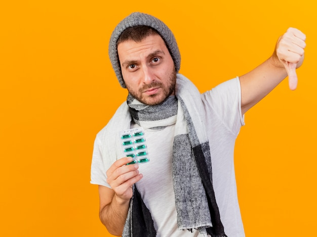 Insatisfait jeune homme malade portant chapeau d'hiver et écharpe tenant des pilules et montrant le pouce vers le bas isolé sur fond jaune