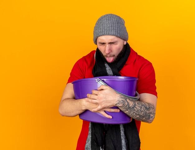 Insatisfait jeune homme malade de race blanche portant un chapeau d'hiver et une écharpe sort la langue et détient un seau en plastique ayant des nausées isolé sur un mur orange avec copie espace