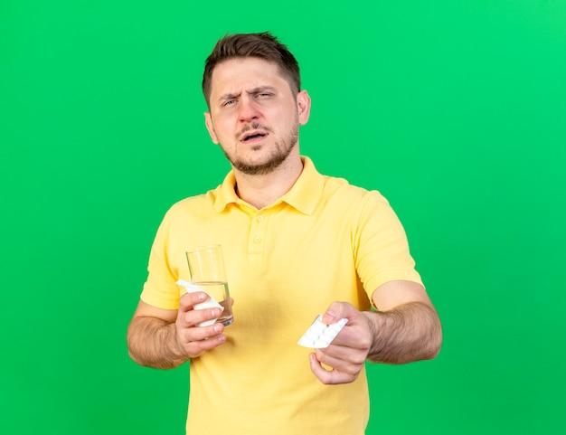 Insatisfait jeune homme slave malade blonde tient un verre d'eau et pack de pilules médicales isolé sur mur vert avec espace copie