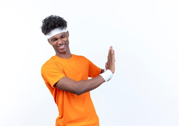 Insatisfait jeune homme sportif afro-américain portant bandeau et bracelet montrant le geste d'arrêt sur blanc