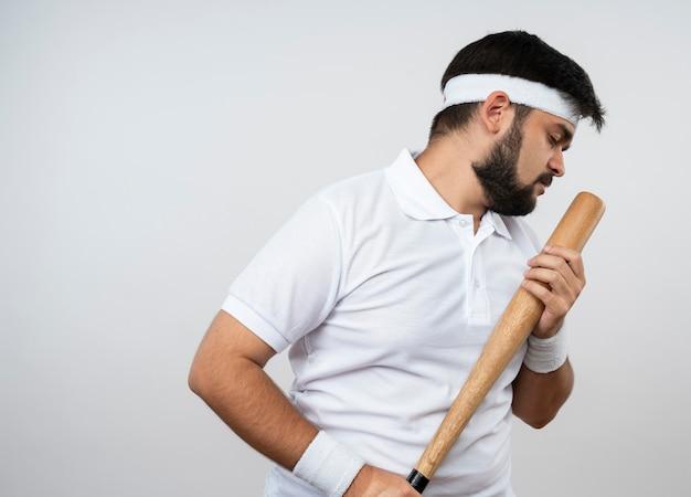 Insatisfait jeune homme sportif aux yeux fermés portant un bandeau et un bracelet tenant une batte de baseball isolé sur un mur blanc avec espace de copie