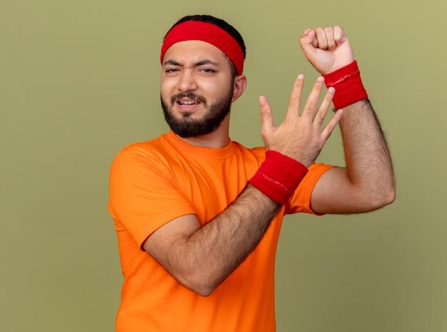 Insatisfait jeune homme sportif portant bandeau et bracelet en levant le poing avec la main isolé sur fond vert olive