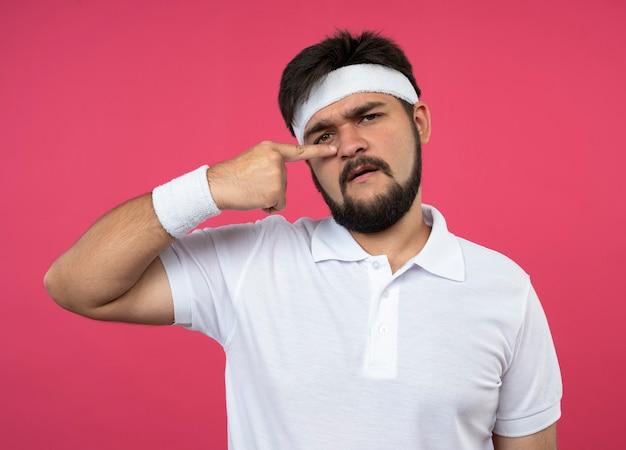 Insatisfait jeune homme sportif portant bandeau et bracelet mettant le doigt sur le nez isolé sur rose