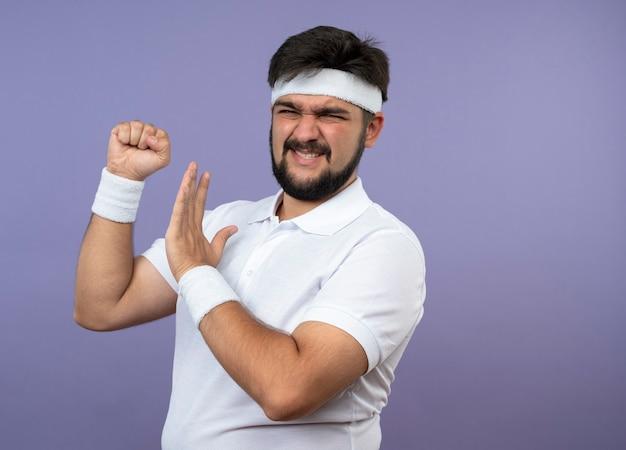Insatisfait jeune homme sportif portant bandeau et bracelet tenant le poing isolé sur mur vert avec espace copie