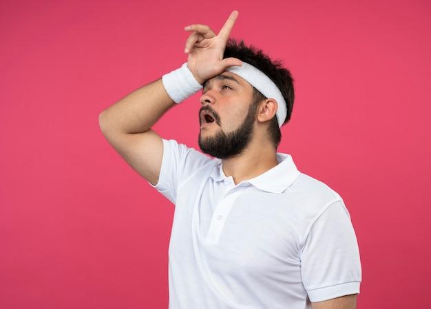 Insatisfait jeune homme sportif regardant côté portant un bandeau et un bracelet montrant le geste du perdant