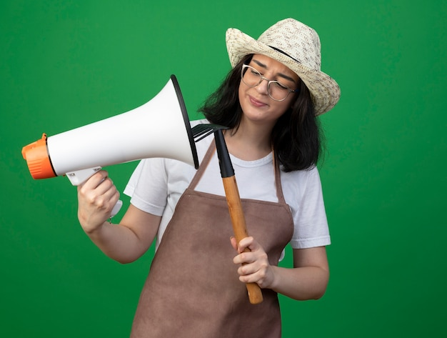 Insatisfait jeune jardinière brune à lunettes optiques et uniforme portant chapeau de jardinage tient et regarde râteau et haut-parleur isolé sur mur vert