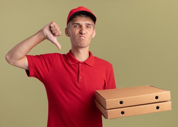 Insatisfait jeune livreur blonde pouces vers le bas et détient des boîtes de pizza sur vert olive